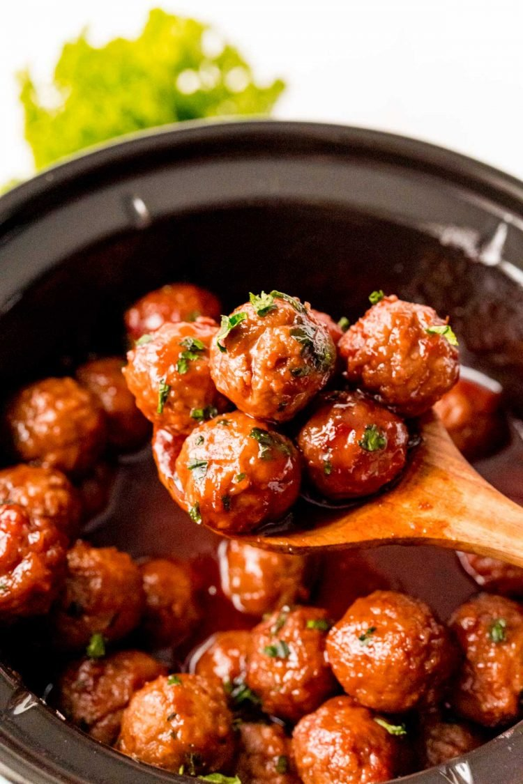 A wooden spoon scooping meatballs out of a crockpot.