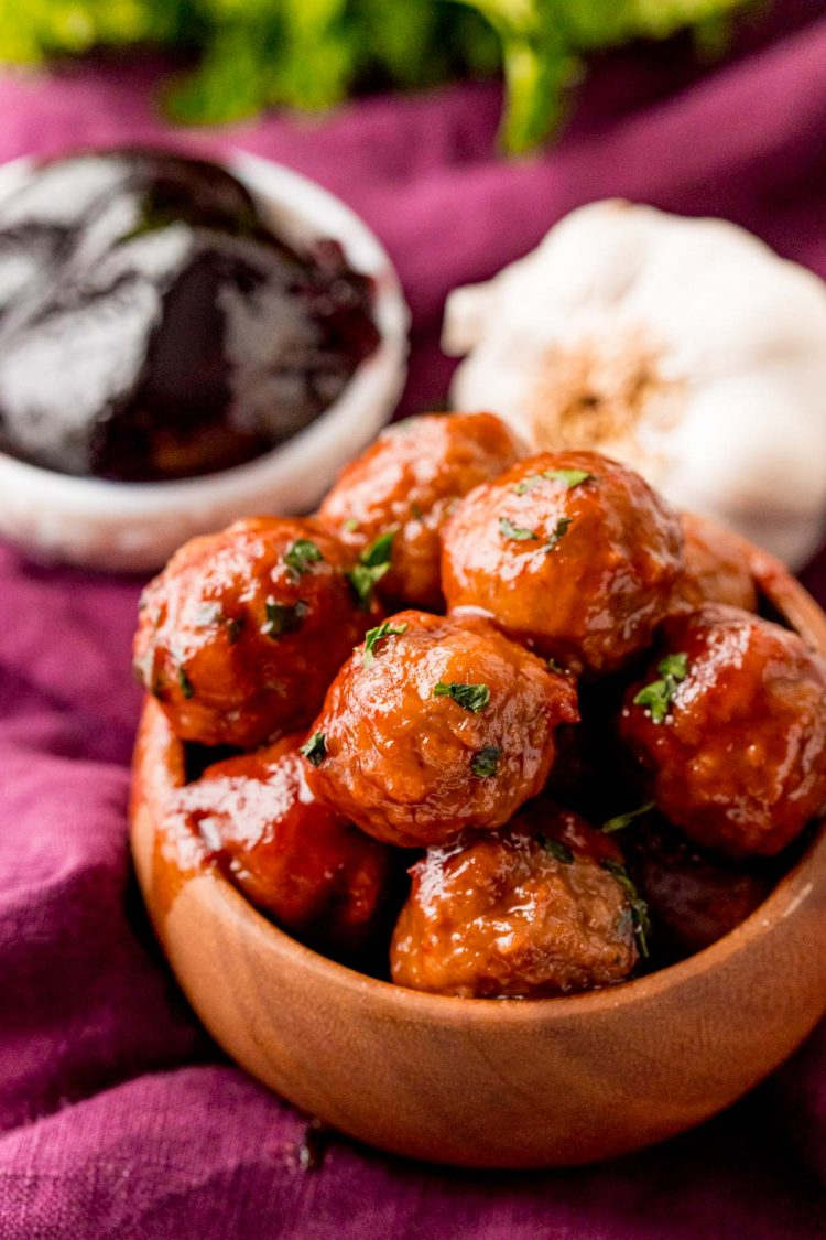 Close up photo of grape jelly meatballs in a brown bowl.