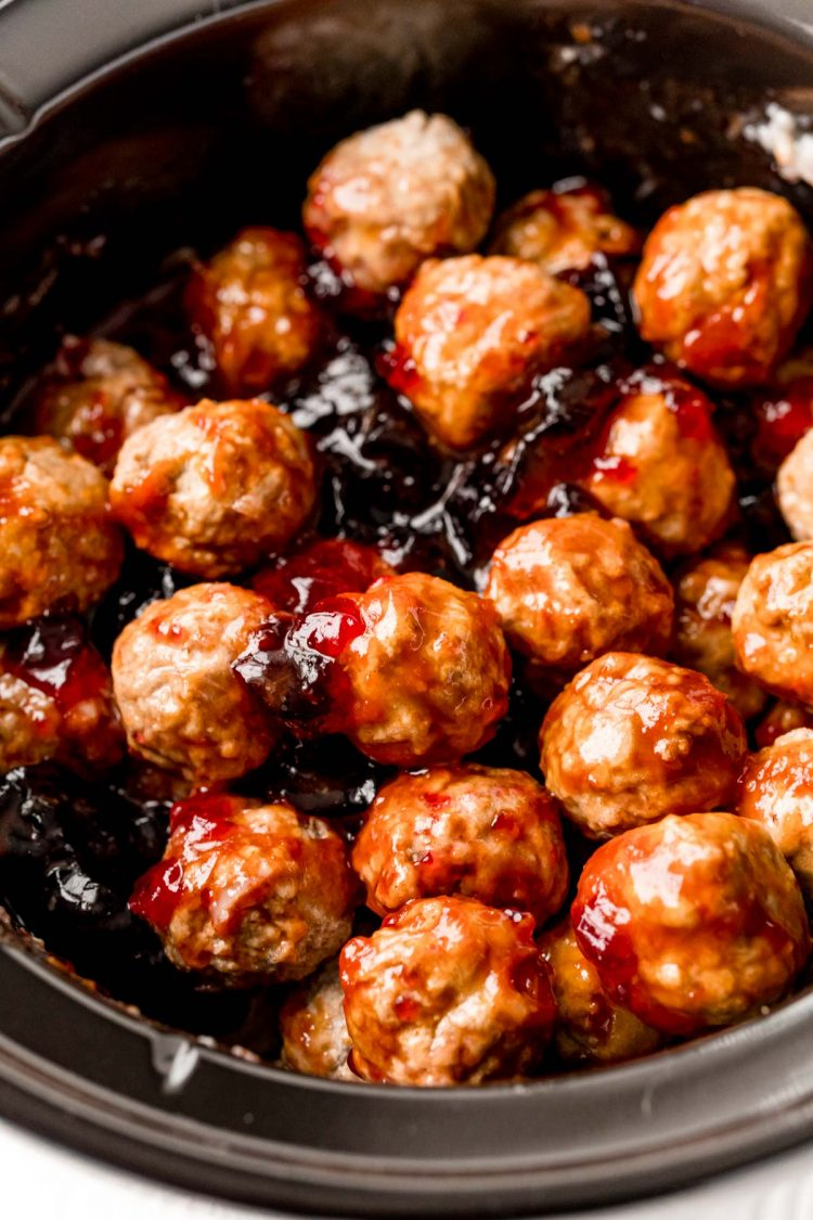 Meatballs in a crockpot with grape jelly.