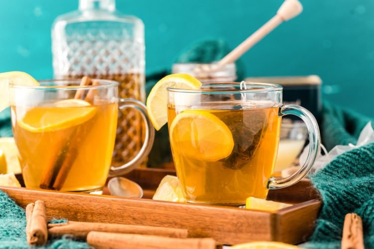 2 mugs on a wooden tray filling with tea, lemon, honey, and whiskey.