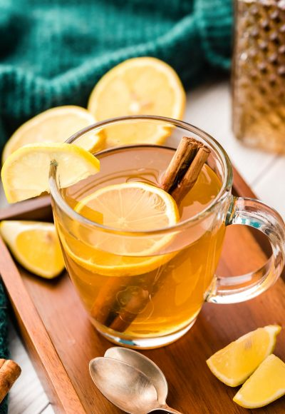 A hot toddy in a clear glass mug with lemon slice and cinnamon stick.