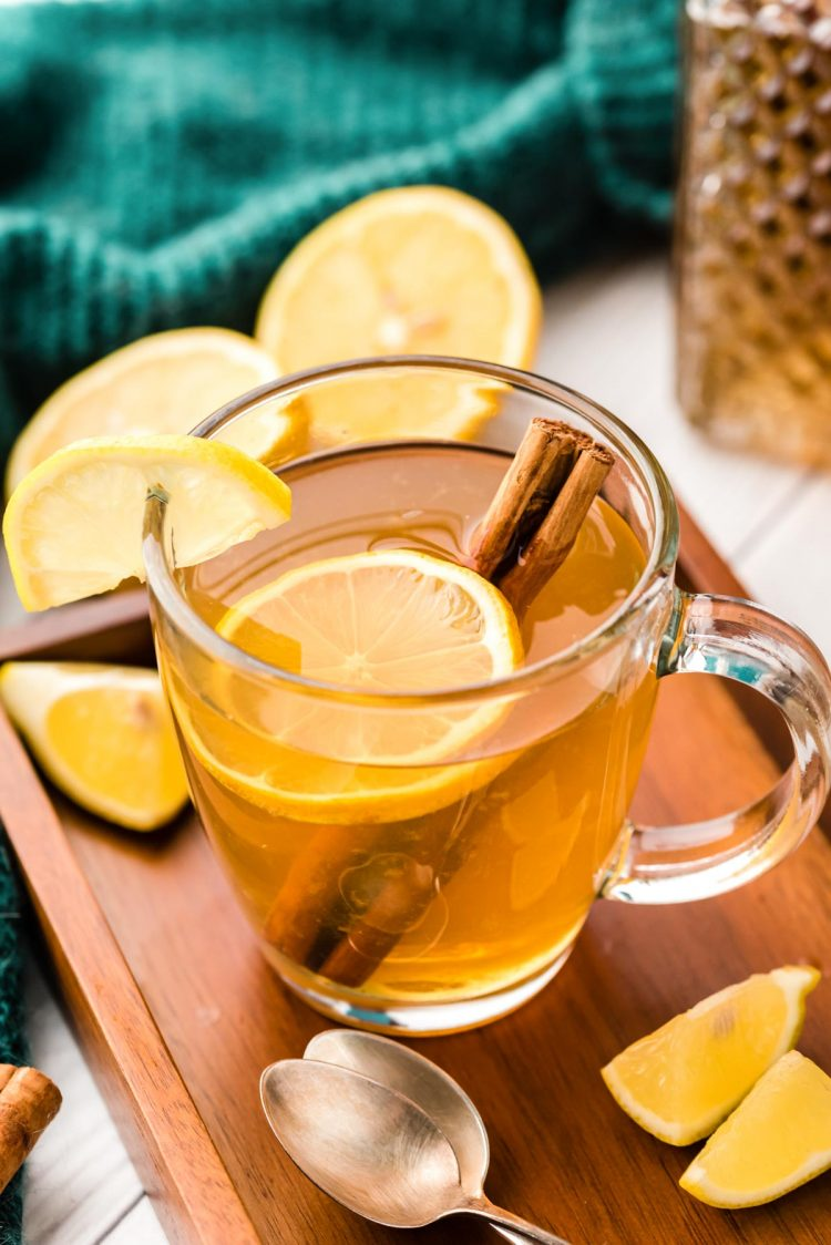 A clear mug filled with a hot toddy with a lemon slice and cinnamon stick.