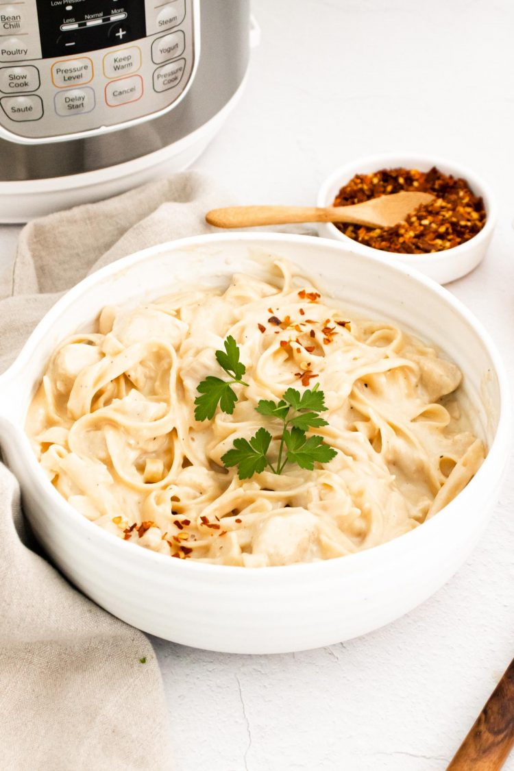 A white bowl of chicken alfredo in front of an instant pot.