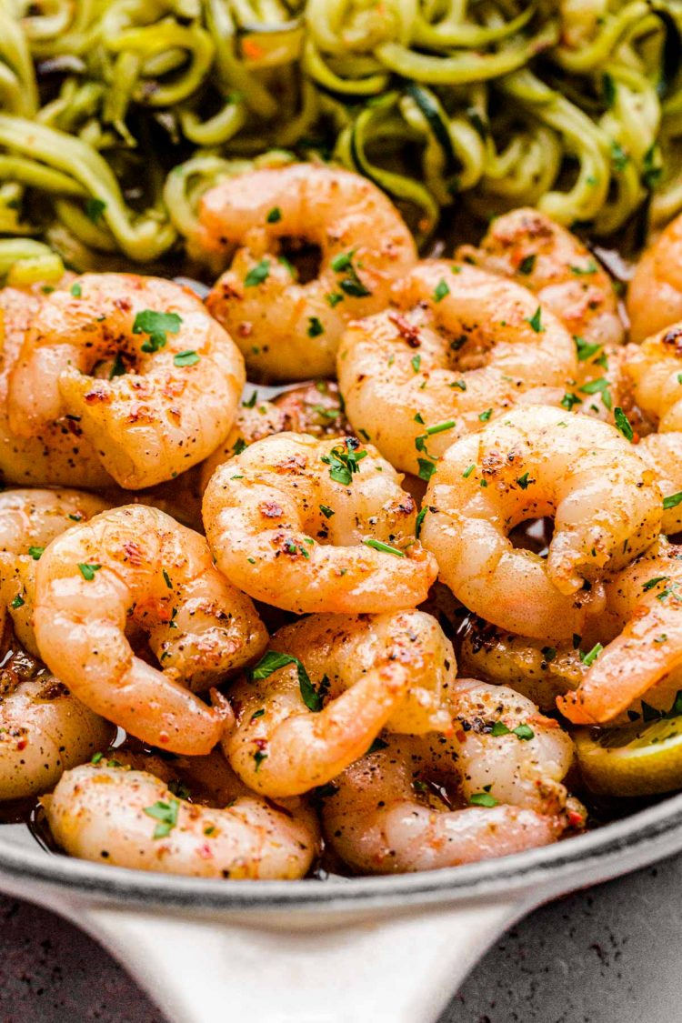Close up photo of garlic lemon shrimp with zucchini noodles in a skillet.