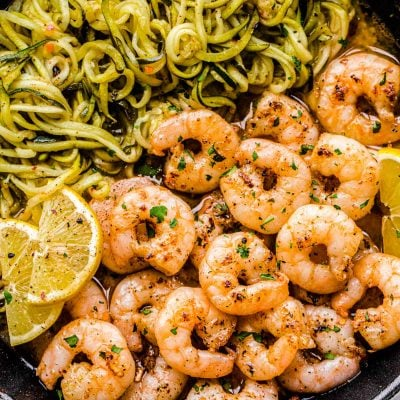 Close up photo of lemon garlic shrimp in a skillet with zucchini noodles and lemon wedges.