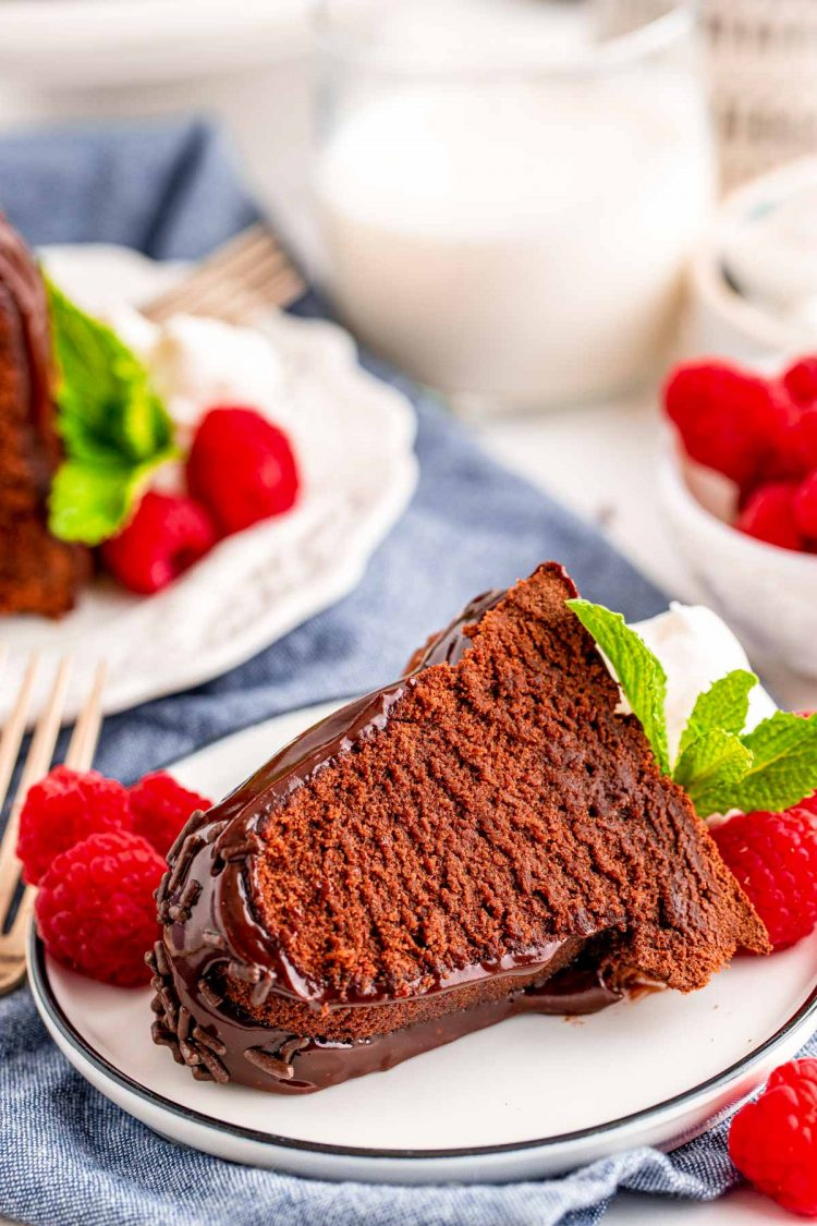A slice of air fryer chocolate cake on a white plate on a blue napkin garnished with raspberries.