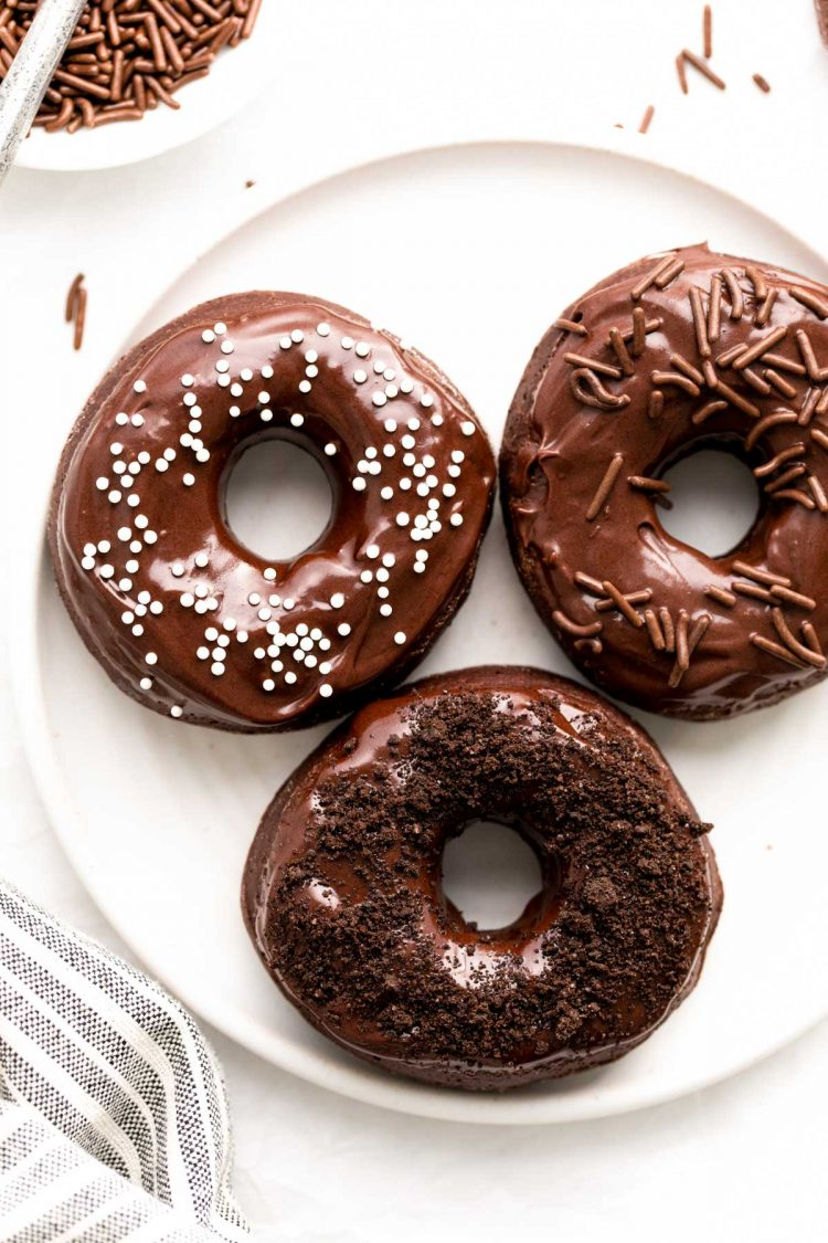 Chocolate frosting donuts on a white plate.