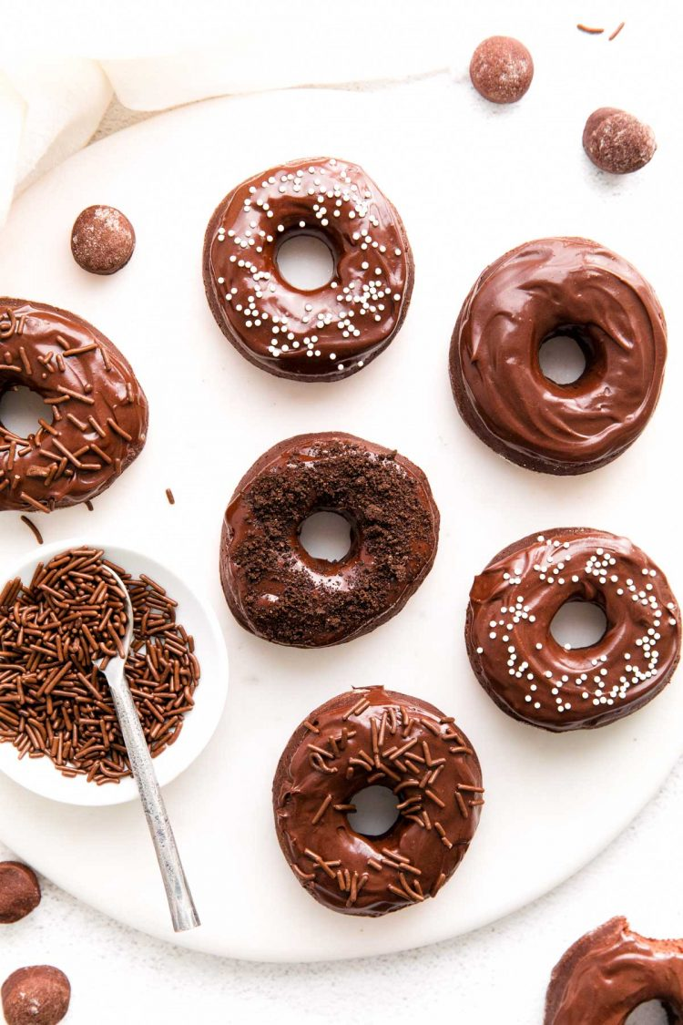 Overhead photo of chocolate donuts on a white serving plate.