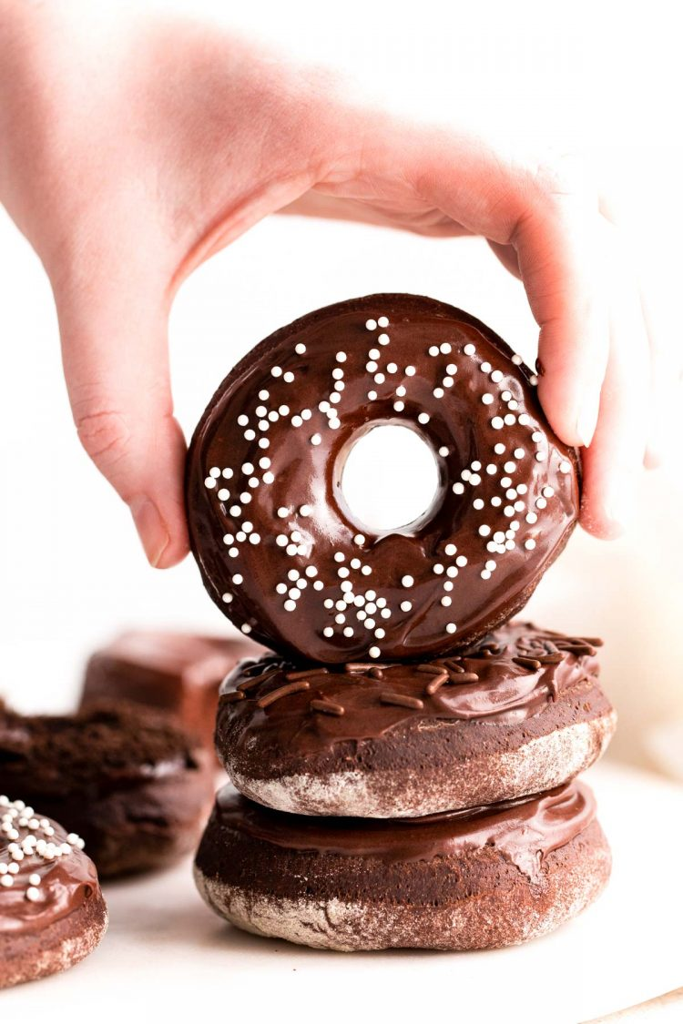 A woman's hand grabbing a chocolate donut off a stack.