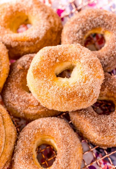 Air fryer cinnamon sugar donuts piled on a wire rack.