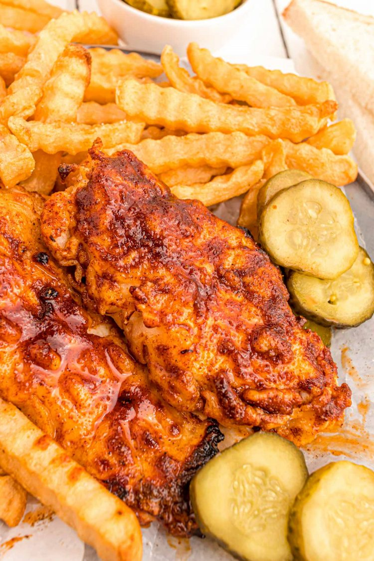 Close up photo of Nashville hot chicken with pickles and fries.