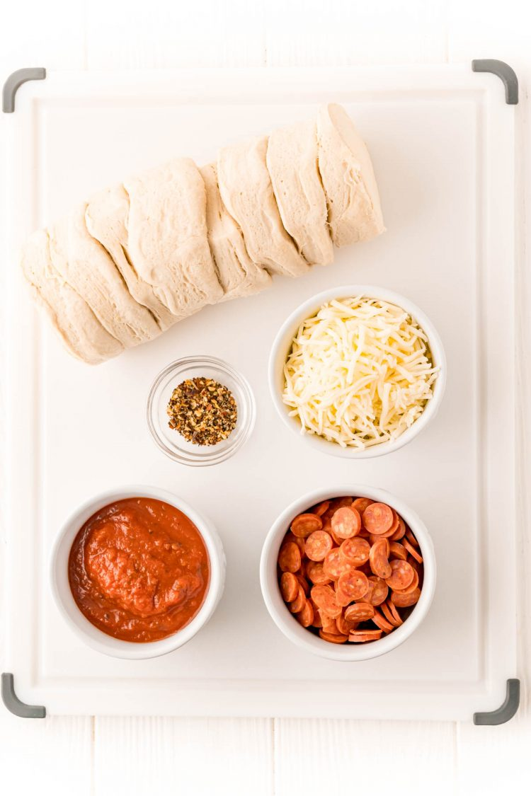 Overhead photo of ingredients to make air fryer pizzas on a white cutting board.