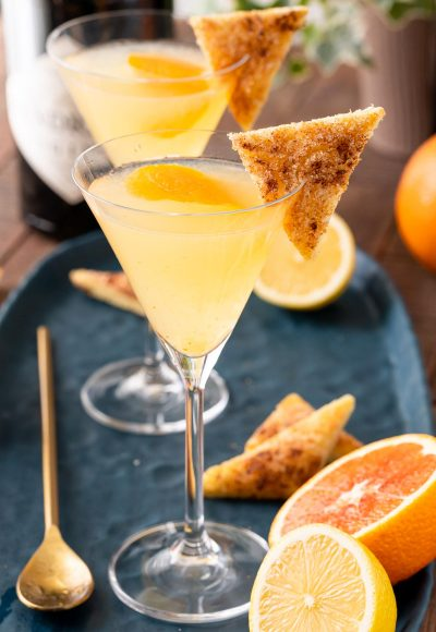 A close up photo of a breakfast martini garnished with cinnamon toast on a blue plate.