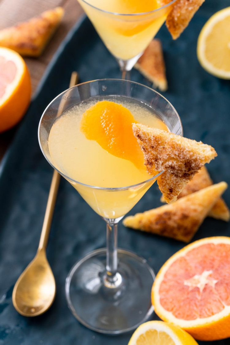 Close up photo of a breakfast martini garnished with cinnamon toast on a blue platter.