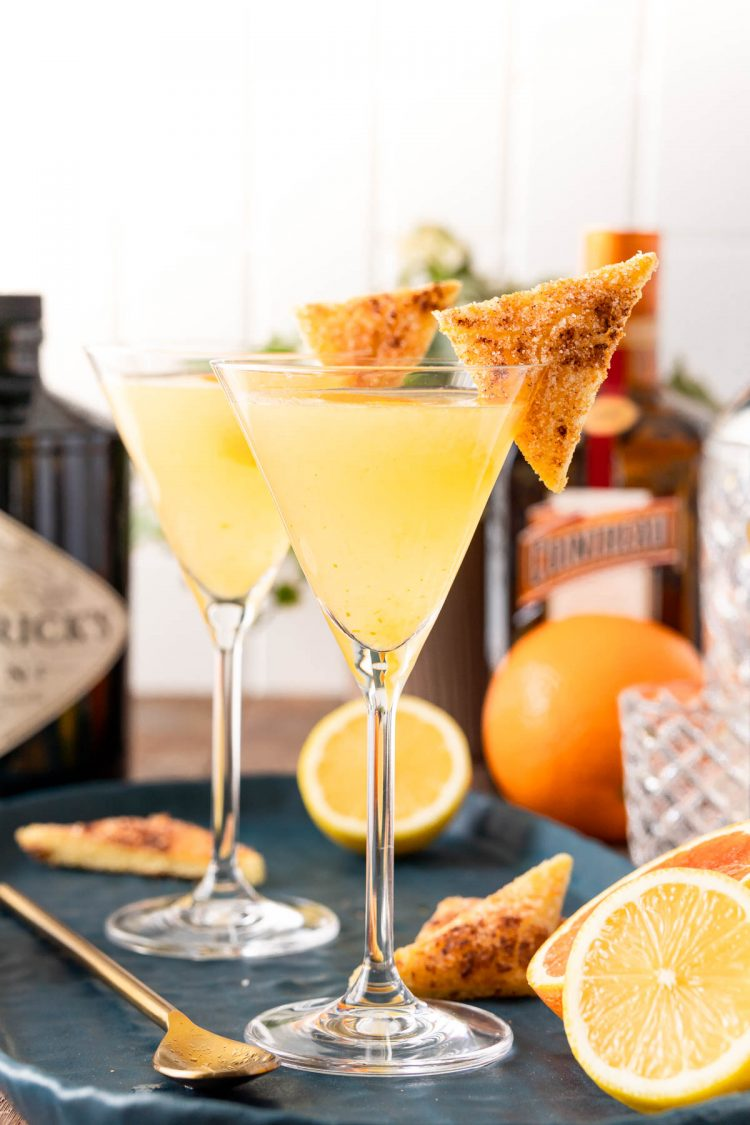 A breakfast martini on a blueb platter with lemons and a bottle of gin in the background.