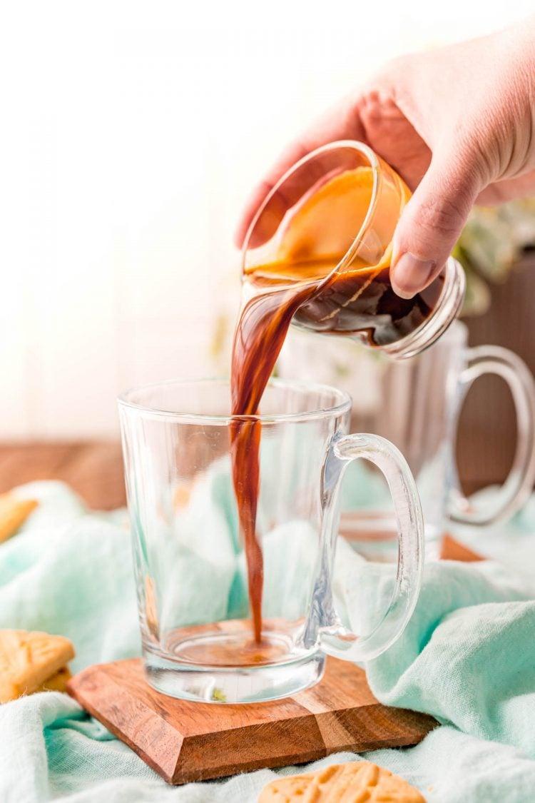 Espresso shot being poured into a glass mug.