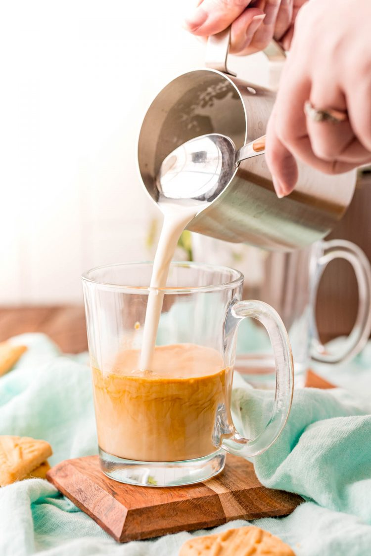 A woman pouring steamed milk into a glass mug with espresso.
