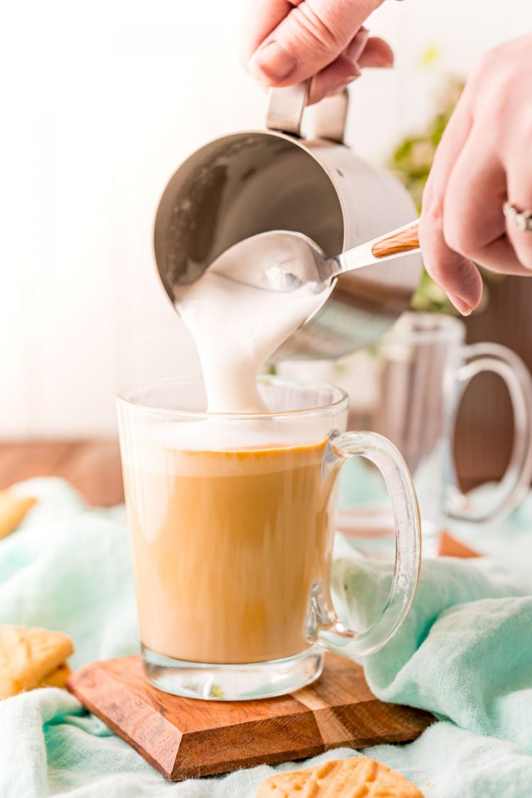 A woman's hand scooping foam out of a milk steaming pitcher onto a latte.