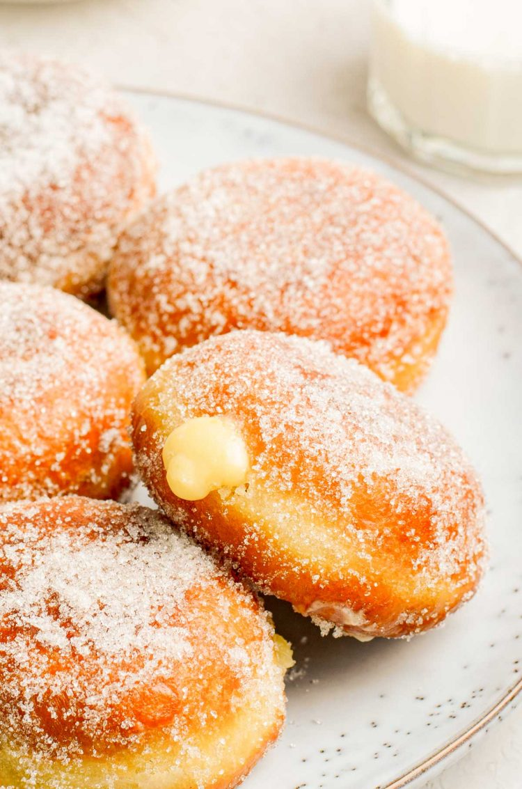 Close up photo of brioche donuts filled with vanilla pastry cream on a plate.
