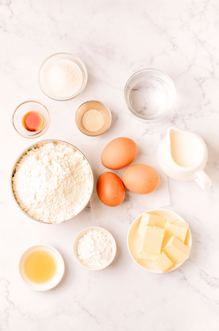 Overhead photo of ingredients needed to make donuts from scratch on a marble counter.