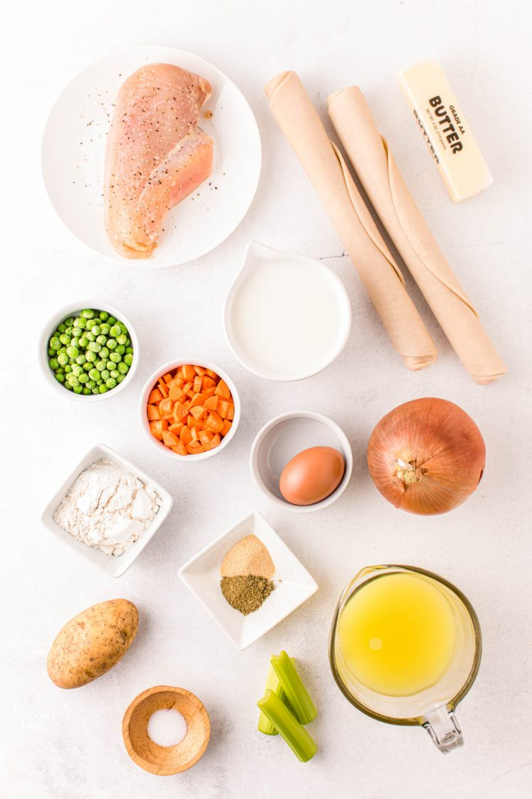 Overhead photo of ingredients to make chicken pot pie on a white counter.