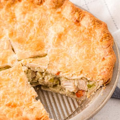 Close up photo of a chicken pot pie with a slice missing out of it.