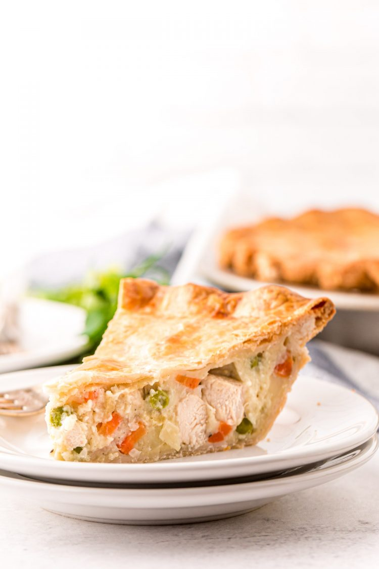 Close up photo of a slice of chicken pot pie on a white plate.