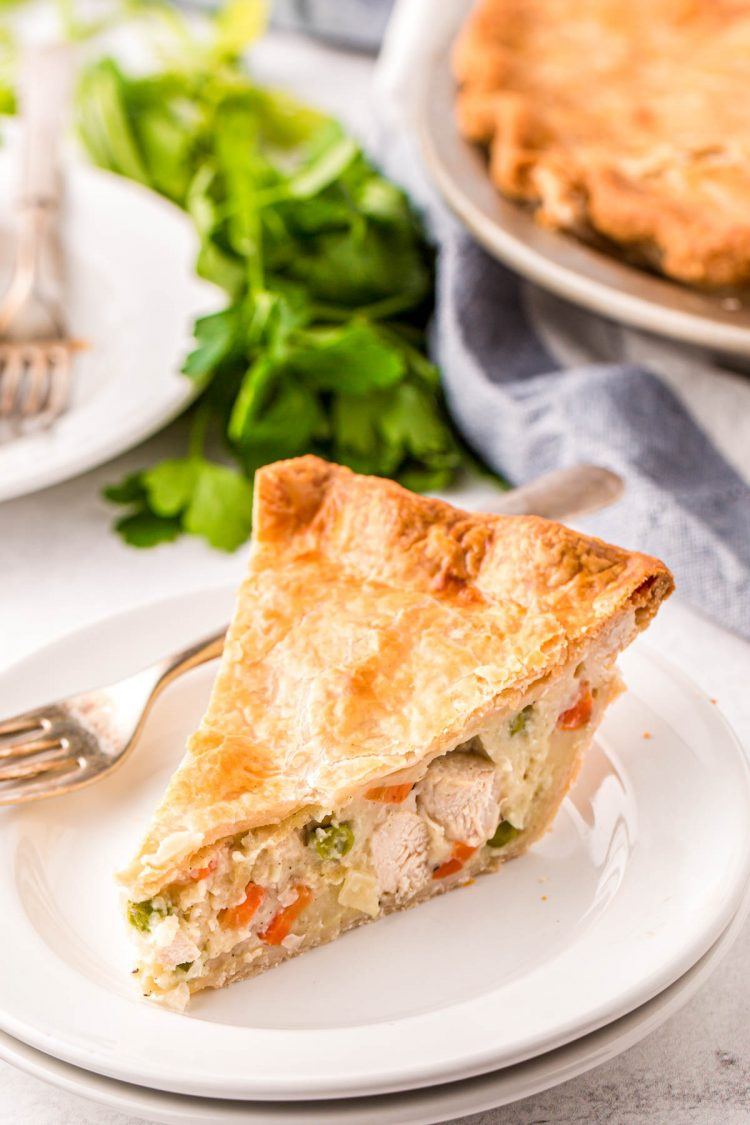 Close up photo of a slice of chicken pot pie on a white plate with a fork.