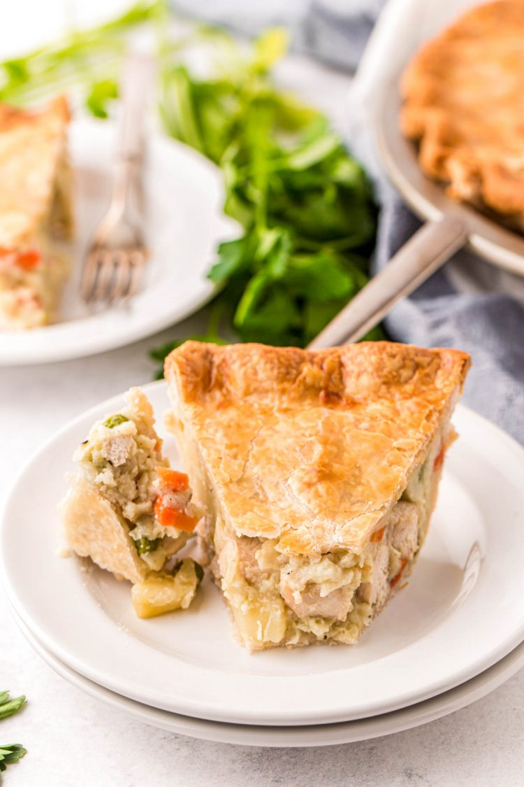 A slice of chicken pot pie on a white plate with a fork with a bite on it.