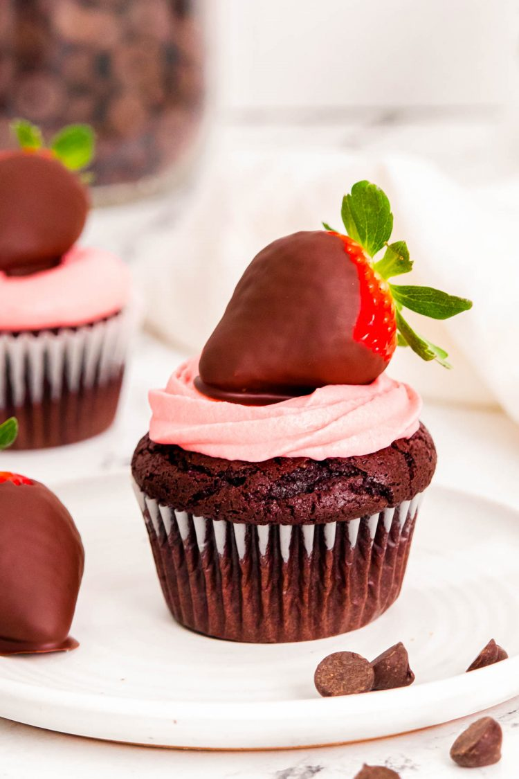 Close up photo of chocolate covered strawberry cupcakes on a white plate.
