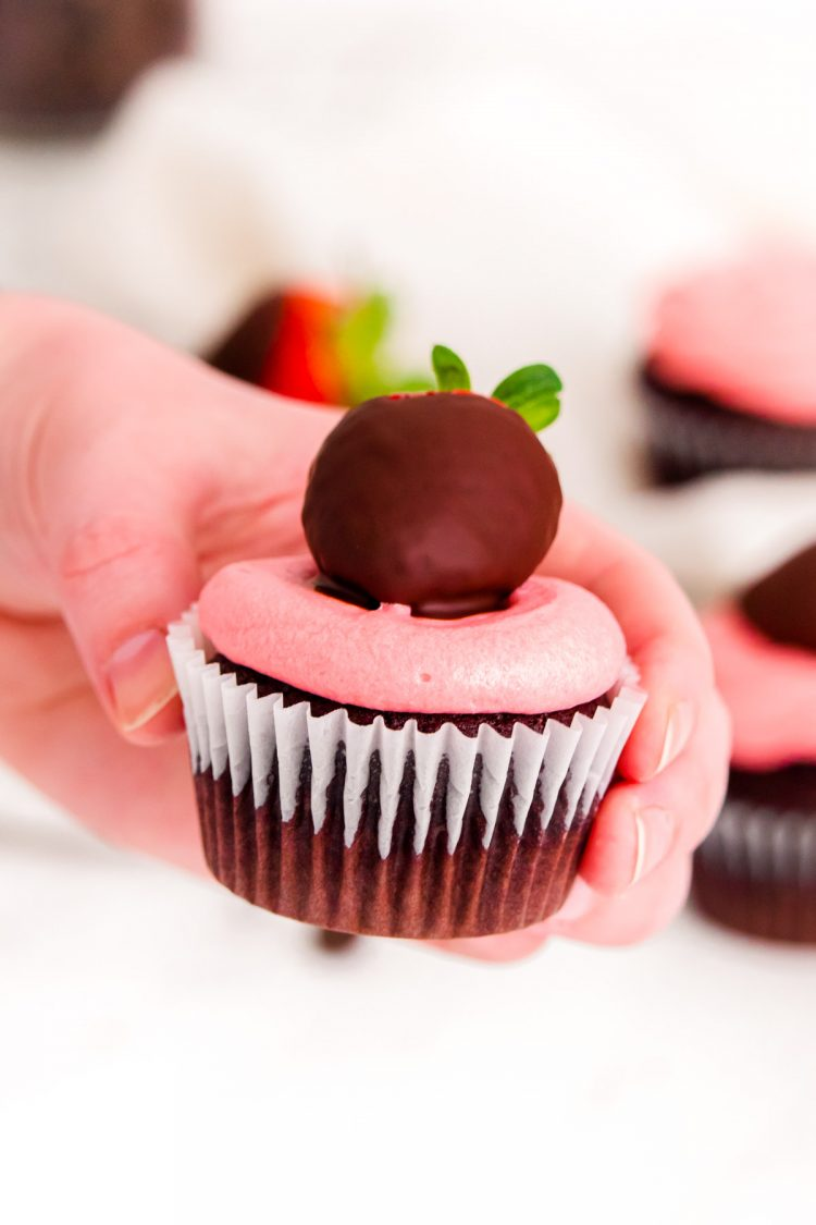 A woman's hand holding a chocolate covered strawberry cupcake.