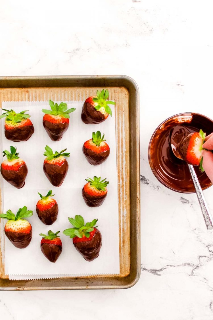 Chocolate covered strawberries on a baking sheet and a woman's hand dipping more in chocolate.