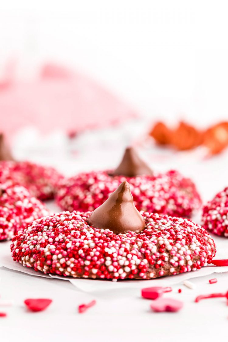 Close up photo of chocolate cookies covered in red, pink, and white sprinkles and topped with a hershey kiss.