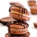 Two peanut butter chocolate macarons stacked on top of a peanut butter cup on a white table.