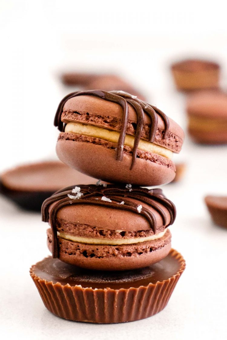 A stack of two peanut butter chocolate macarons on top of a peanut butter cup.