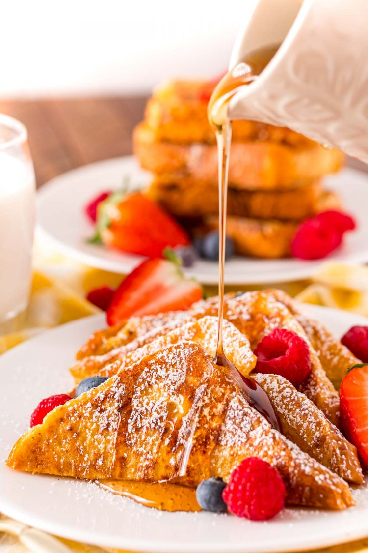 Maple syrup being poured over the top of a plate of French toast with berries.