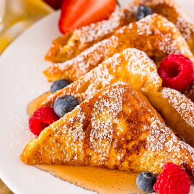Close up photo of french toast on a white plate with berries and syrup.