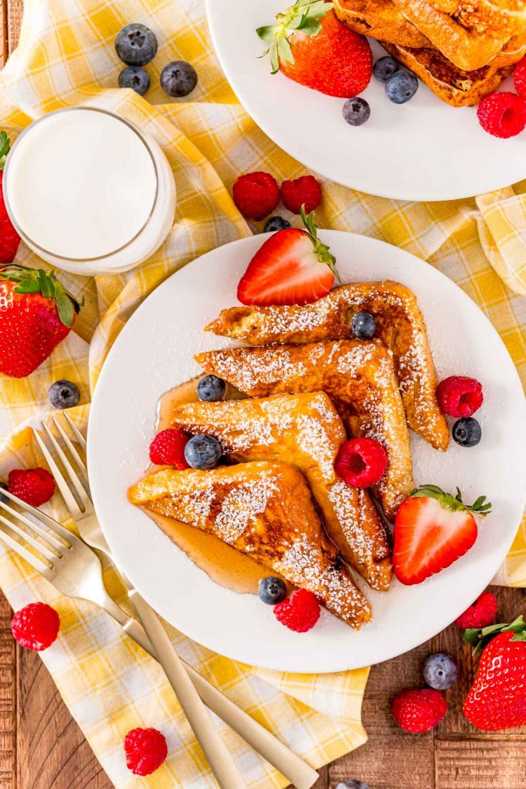 Overhead photo of a plate of french toast that has been slices into triangles and topped with powdered sugar, syrup, and fruit on a yellow napkin with milk next to it.
