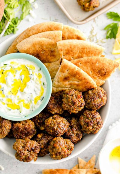 Overhead close up photo of Greek meatballs in a bowl with pita bread and tzatziki sauce.