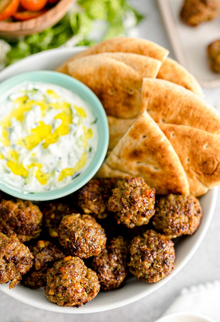 Close up photo of Greek meatballs in a bowl with tzatziki sauce and pita bread.