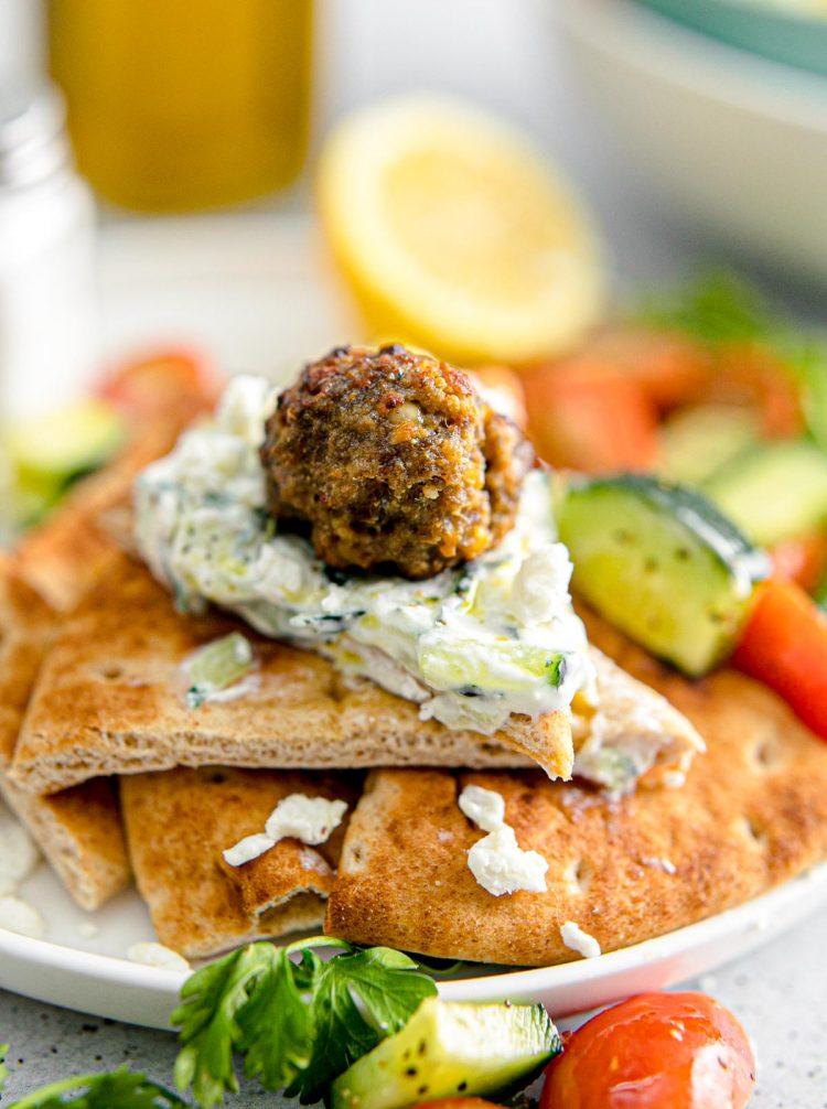 Greek meatballs with tzatziki sauce on pita bread.