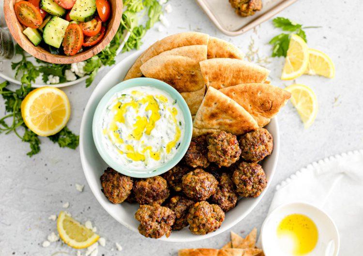 Overhead photo of Greek meatballs with tzatziki sauce and pita bread.