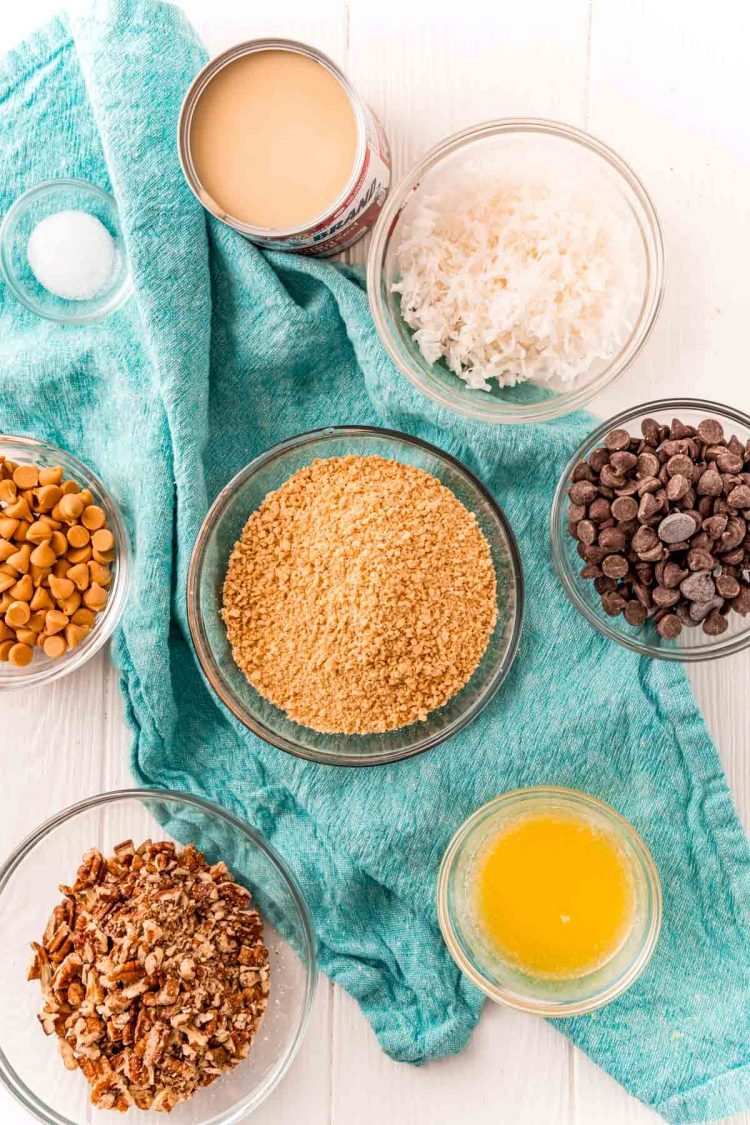 Ingredients to make hello dolly or seven layer bars on a white table with a blue napkin.