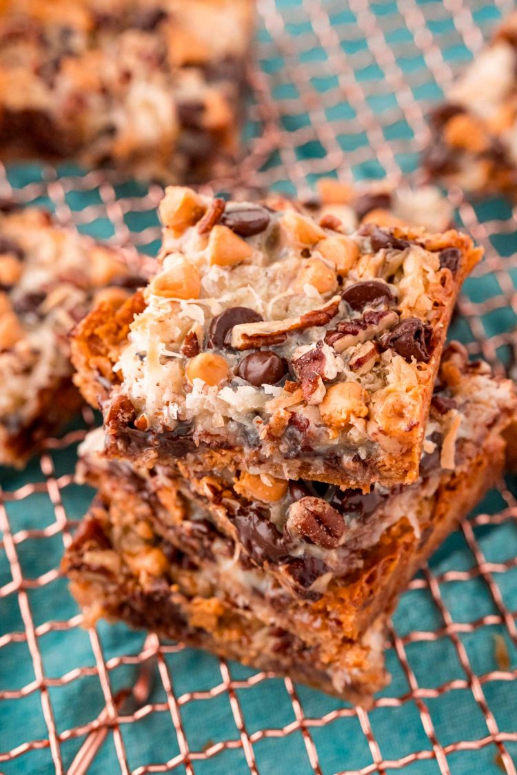 Close up photo of Hello Dolly Bars stacked on a copper wire rack.