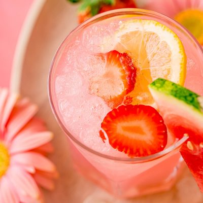 A close up photo of a glass with a pink cocktail in it garnished with strawberries and lemon.