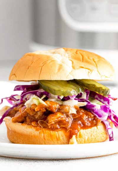 Close up photo of a bbq chicken sandwich with coleslaw and pickles with an instant pot in the background.