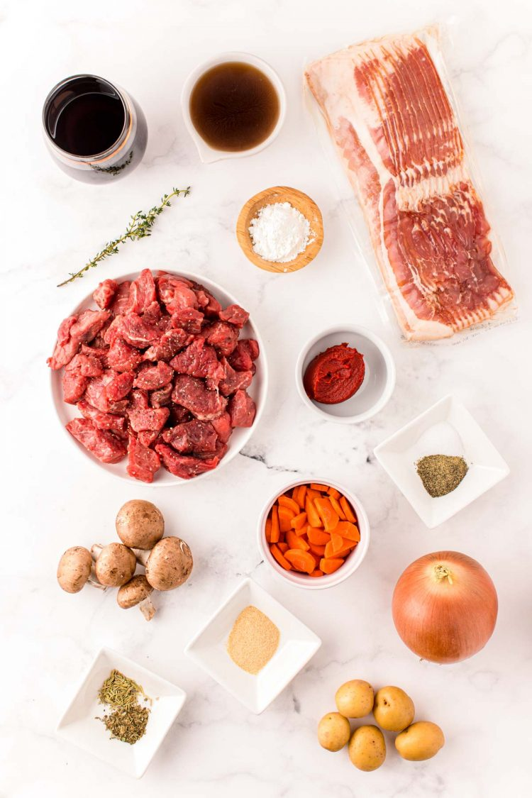 Overhead photo of ingredients to make beef bourguignon in an instant pot on a white table.
