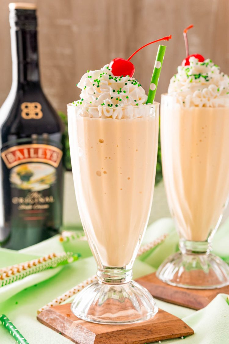 Two Irish cream milkshakes on wood coasters on a green napkin with a bottle of Bailey's in the background.