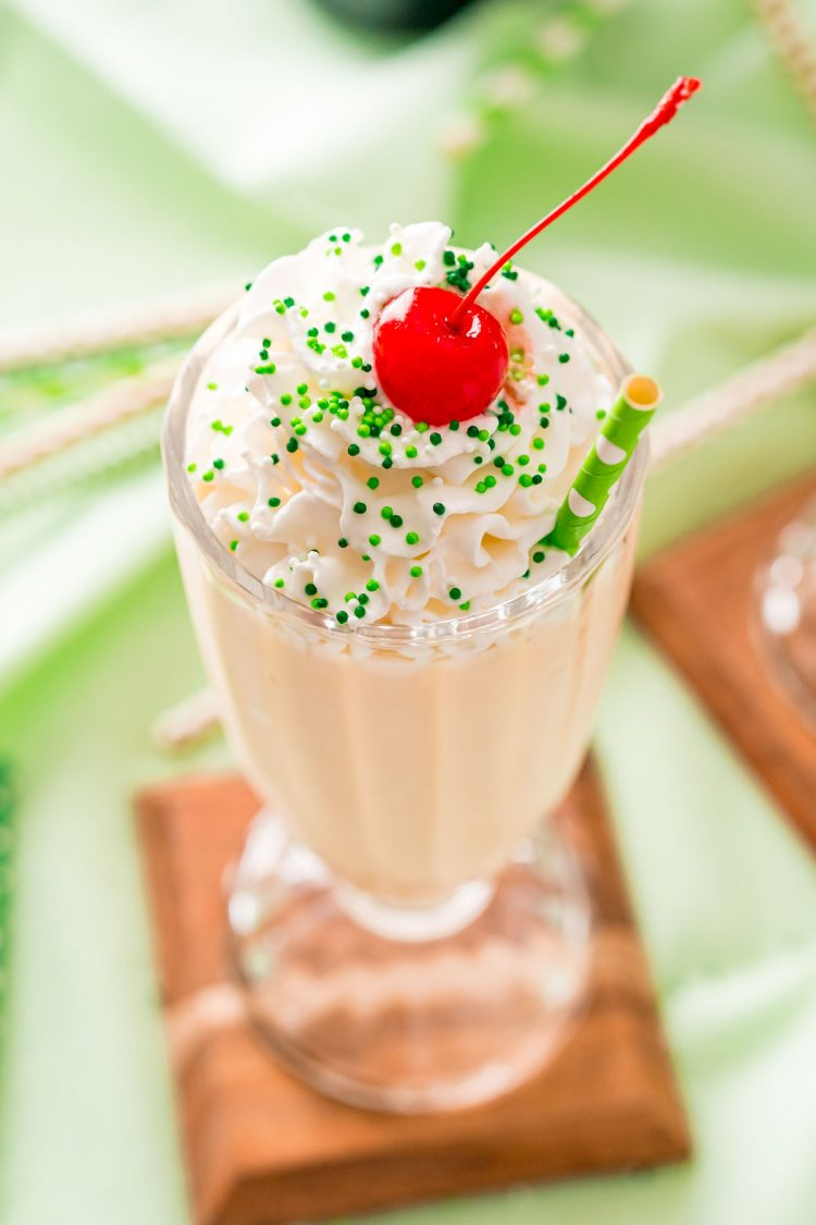 Close up photo of a milkshake glass filled with a Bailey's milkshake and topped with whipped cream and a cherry on a green napkin.