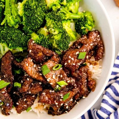 Overhead photo of mongolian beef with broccoli and rice in a white bowl.